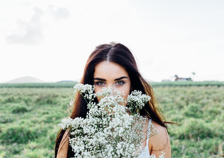 Gesund leben dargestellt durch Frau in der Natur mit Blumen in der Hand.